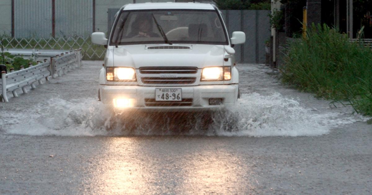 A man drives his car through floodwater triggered by Typhoon Talas at Higashiyama on September 3, 2011 in Himeji, Japan.</p>