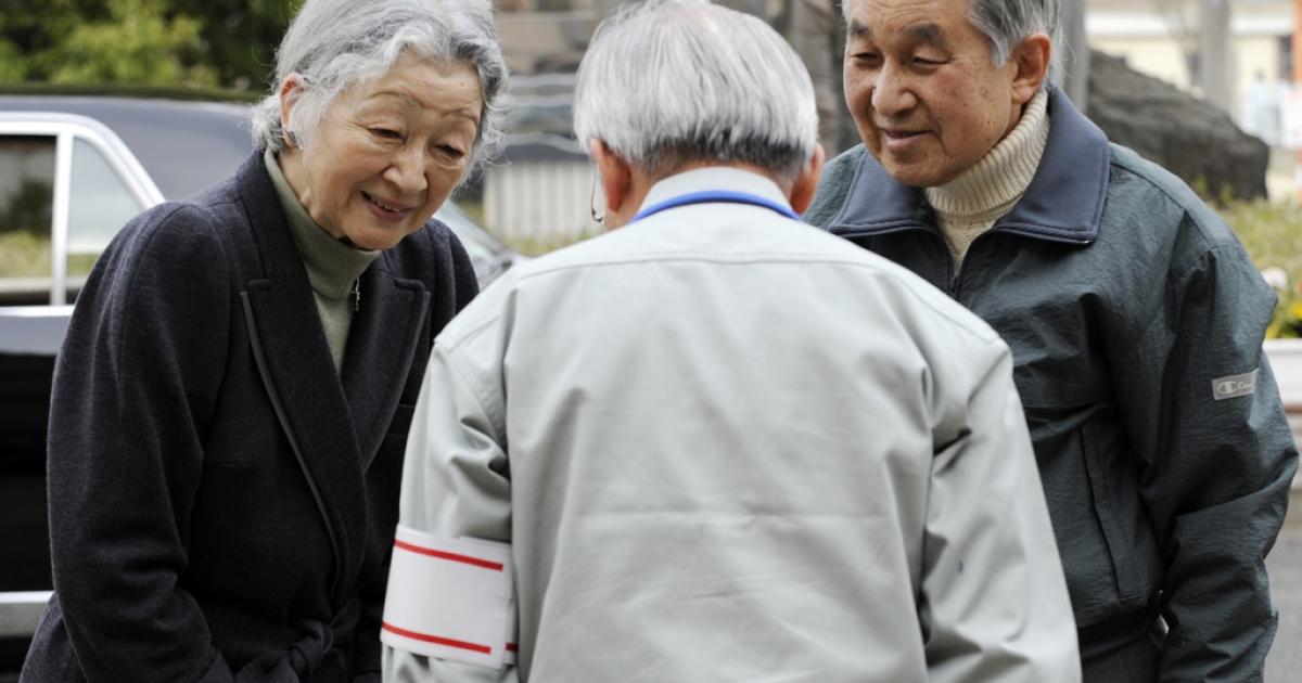 Japanese Emperor Akihito (R) and Empress Michiko (L) speak with Futaba town mayor Katsutaka Idogawa (C) while visiting the Futaba town residents' makeshift shelter in Kazo, Saitama prefecture, on April 8, 2011.</p>