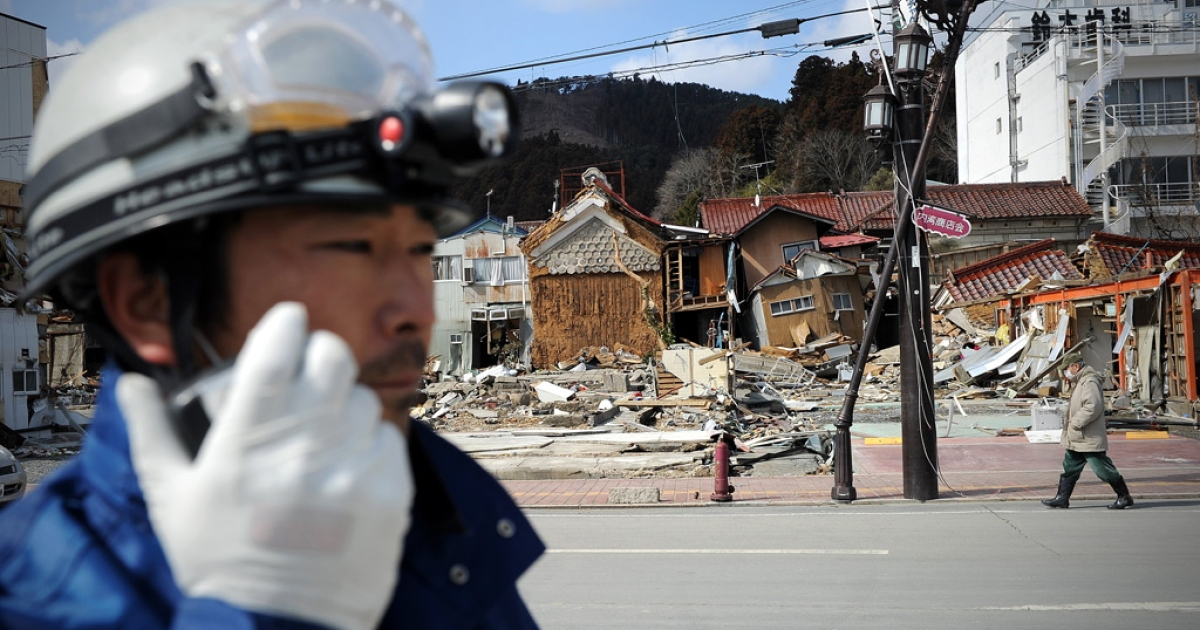 A Japanese rescue worker holds a walkie talkie as a survivor walks past collapsed buildings in Kesennuma in Miyagi prefecture on March 18, 2011 one week after a massive earthquake and tsunami devastated northeastern Japan.</p>