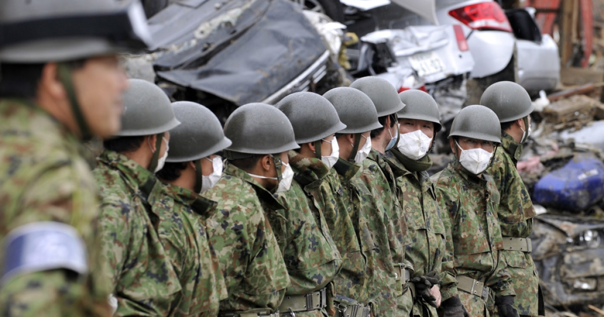 Members of the Ground Self-Defense Forces form a line before a silent prayer for the tsunami victims in Kesennuma, Miyagi prefecture on April 11, 2011 a month after the earthquake and tsunami strike.</p>