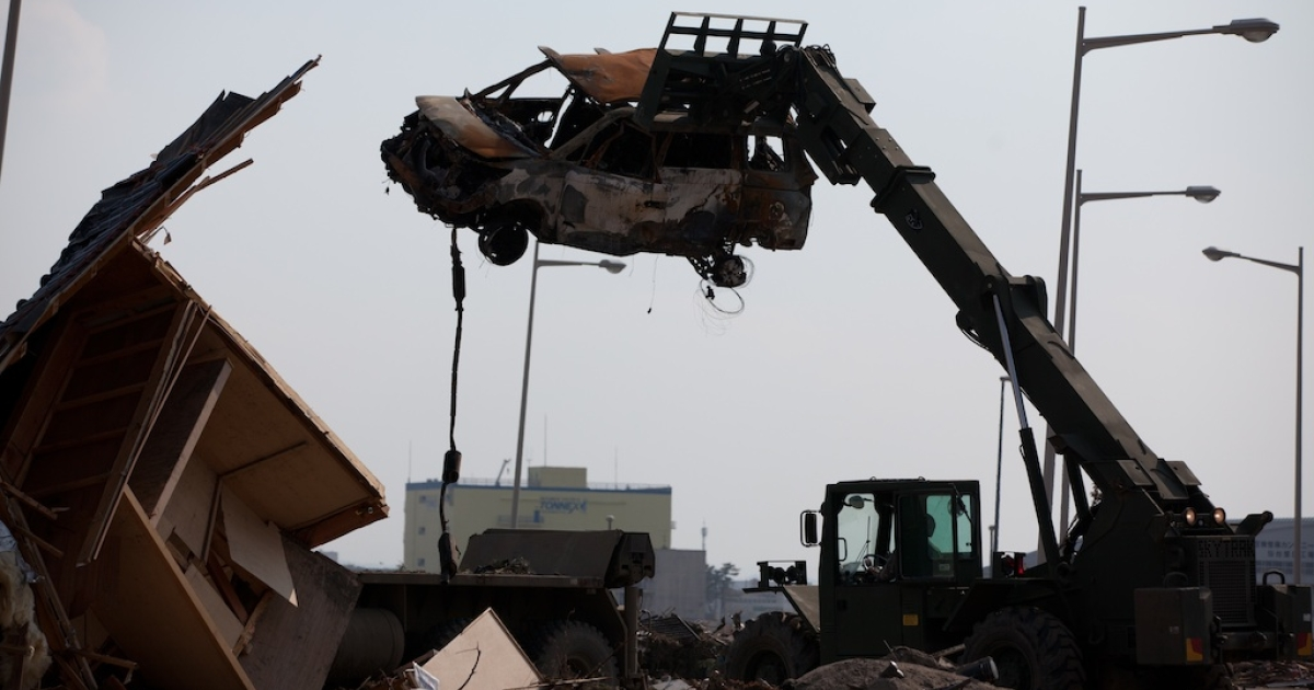 A U.S. military forklift carries a destroyed vehicle at a loading bay platform at Sendai Airport in Miyagi prefecture, Japan, on March 29, 2011.</p>