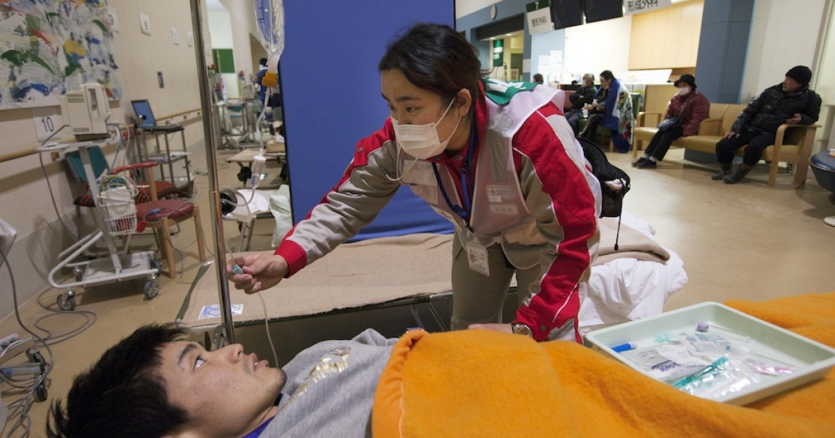 A worker with the Japanese Red Cross takes care of a patient coming from the earthquake shelters at the Ishinomaki hospital March 28, 2011, in Ishinomaki, Japan.</p>