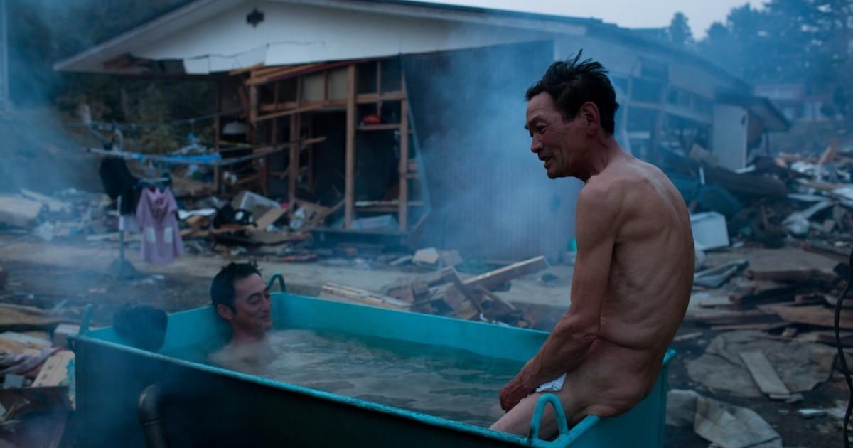 Residents take an outdoor bath amongst tsunami devastation in Kesennuma city, Miyagi prefecture on April 14, 2011.</p>