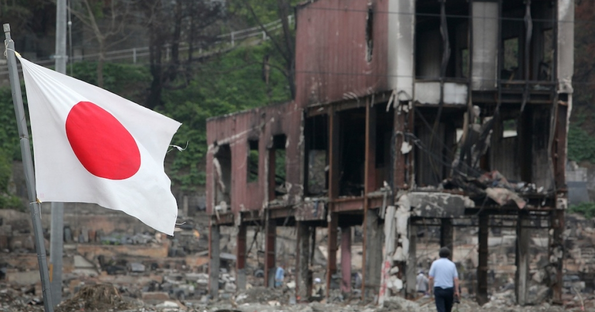 A man walks through debris as the Japanese national flag flies on June 12, 2011, in Otsuchi, Iwate, Japan.</p>