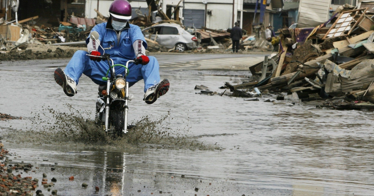 A man rides a motorcycle through water in Ishinomaki city, Miyagi prefecture on April 8, 2011. A powerful aftershock that rocked an area of Japan still reeling from last month's earthquake and tsunami disaster killed two people and injured more than 100, emergency services said.</p>