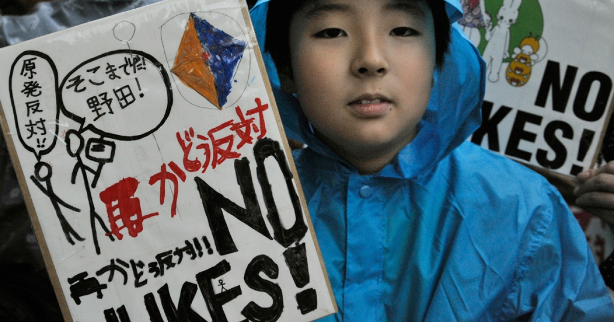 A boy holds a banner denouncing nuclear power plants during a protest in front of the official residence of Japanese Prime Minister Yoshihiko Noda in Tokyo on July 20, 2012.</p>