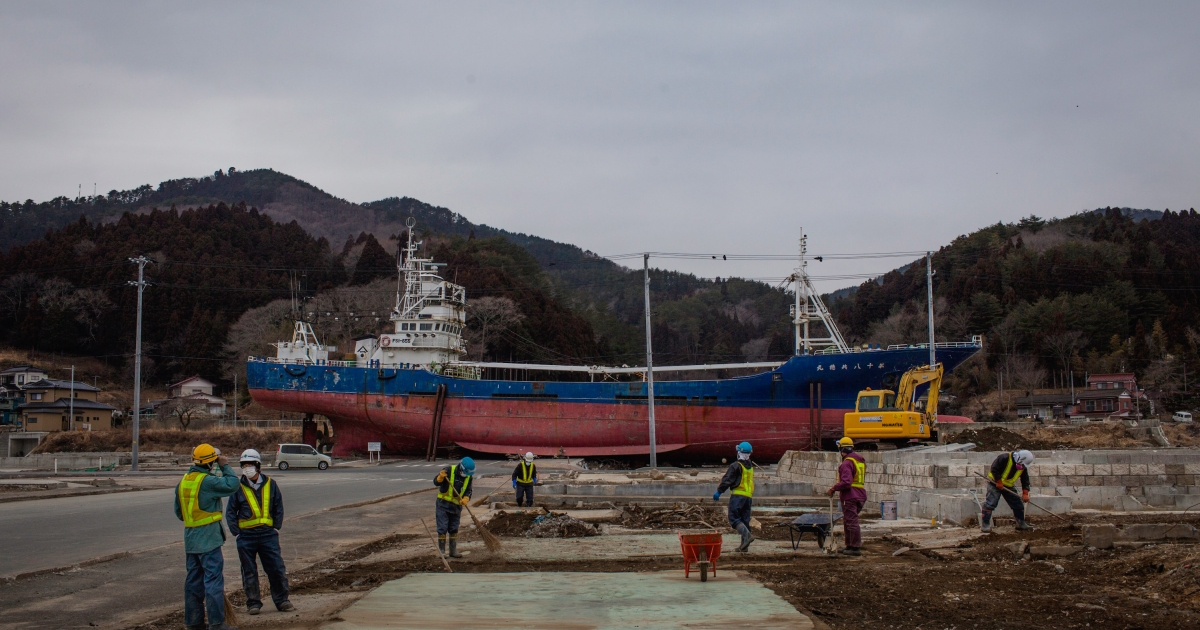 Workers clean debris fdestroyed houses in front of a large fishing boat washed onto land during last year's tsunami on March 08, 2012 in Kesennuma, Japan. The Japanese government faces an uphill battle with the need to dispose of rubble as it works to rebuild economies and livelihoods.</p>