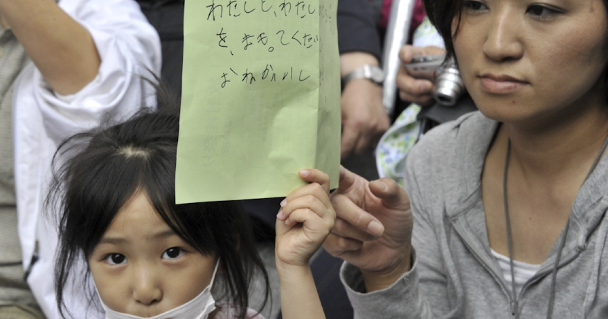 A girl holds her petition to ask the education ministry to protect children from radioactive contamination at Fukushima prefecture during a rally at the Education Ministry in Tokyo on May 23, 2011. Some 400 civic group members, including 60 parents and children from Fukushima, demanded to review the radiation limit of 3.8 microsieverts per an hour as the education ministry has set a radiation limit to allow children in Fukushima.</p>
