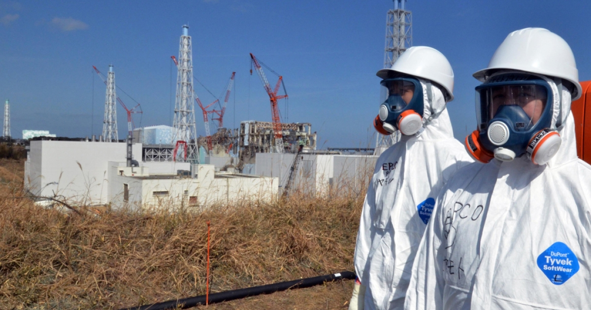 This file picture taken on February 28, 2012 shows workers standing near the stricken Tokyo Electric Power Co (TEPCO) Fukushima Daiichi nuclear power plant in Okuma, Fukushima prefecture. As of March 8, 2012, Japan has closed all but two of its nuclear reactors following the disaster at Fukushima's power plant. The remaining two may be closed within the next month.</p>