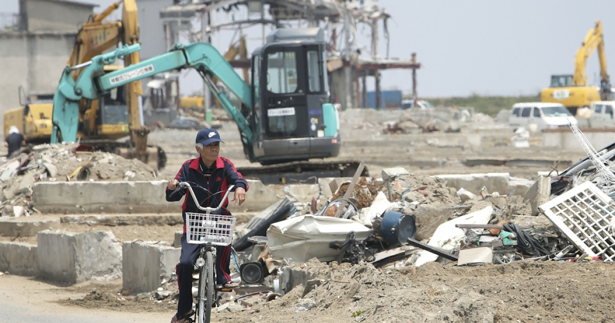 A man cycles past debris that is being removed by heavy machinery, three months and two days after the magnitude 9.0 earthquake and tsunami on June 13, 2011 in Natori, Miyagi, Japan. Tokyo is expected to bid to host the 2020 Summer Olympics, and would include the hard-hit prefectures of Miyagi, Iwate and Fukushima.</p>