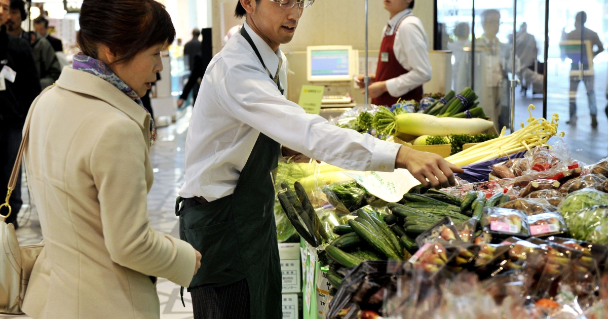 A shop clerk (C) helps a shopper (L) with some produce for sale, grown in Ibaraki, Chiba, Tochigi and Gunma prefectures north of the Japanese capital, an area affected by the nuclear crisis to the Fukushima nuclear power plant, at Tokyo's Daimaru department store on April 6, 2011. The store was offering the produce to customers to support Japanese farmers hurting from dropped sales due to rumors of the spread of radiation.</p>