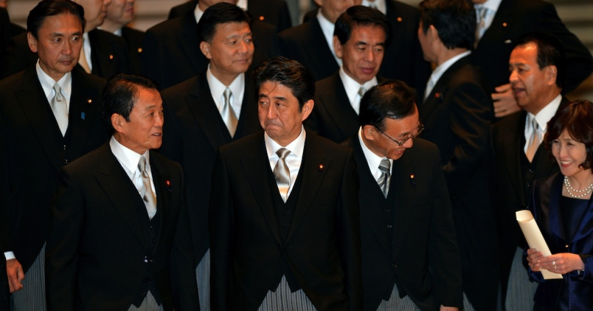 Japan's new Prime Minister Shinzo Abe (C), accompanied by Finance Minister Taro Aso (3L) and Justice Minister Sadakazu Tanigaki (2nd R), waits for his vehicle after a photo session with his cabinet members as they were inaugurated before Emperor Akihito at the Imperial Palace in Tokyo on December 26, 2012. Abe was elected Japan's prime minister by the lower house of parliament after he swept to power on a hawkish platform of getting tough on diplomatic issues while fixing the economy.</p>