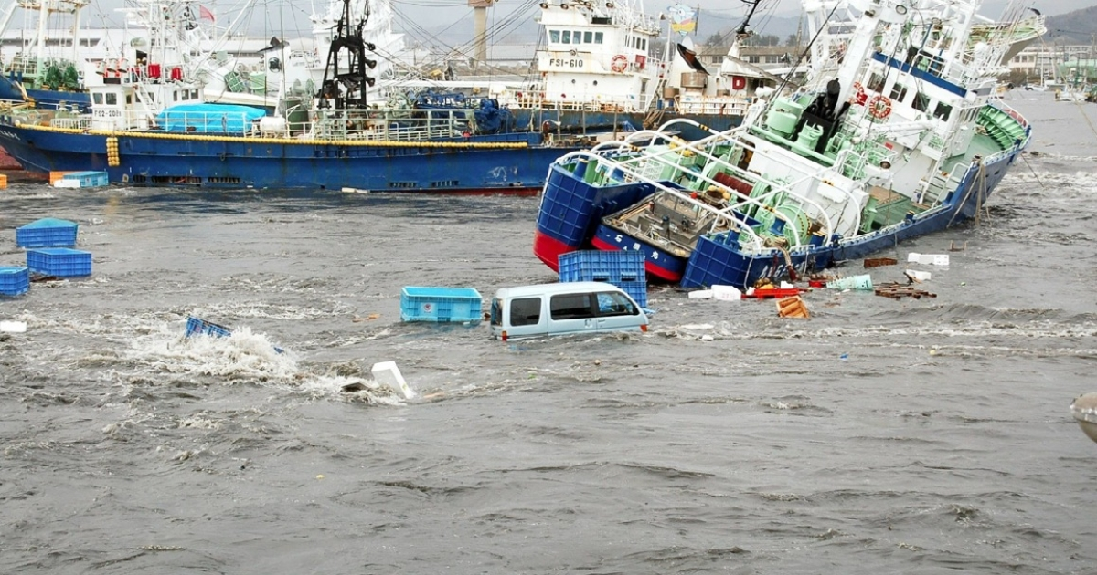 Fishing boats and vehicles are carried by a tsunami wave at Onahama port in Iwaki city, in Fukushima prefecture, northern Japan on March 11, 2011.</p>