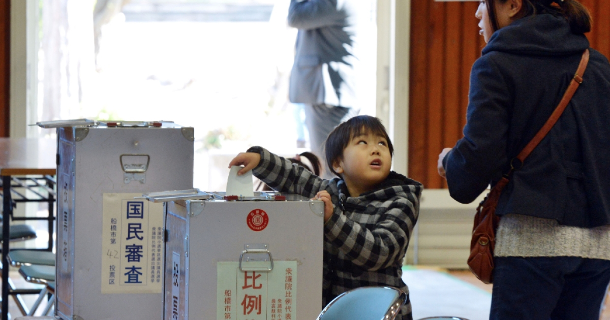 A boy helps his mother (R) to cast a vote in the general election at a polling station in Funabashi, suburban Tokyo on December 16, 2012. Voters began casting ballots in Japan for a general election likely to return long-ruling conservatives to power after three years in the wilderness.</p>
