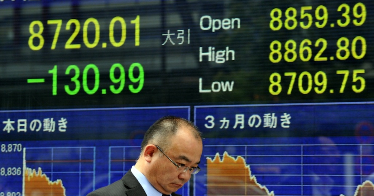 A businessman passes before a share prices board in Tokyo on July 12, 2012.</p>