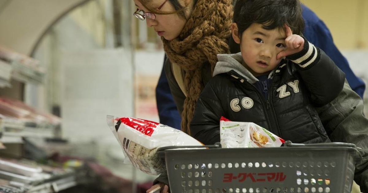 A woman and child shop at a supermarket in Sendai, Miyagi prefecture, on March 20, 2011.</p>
