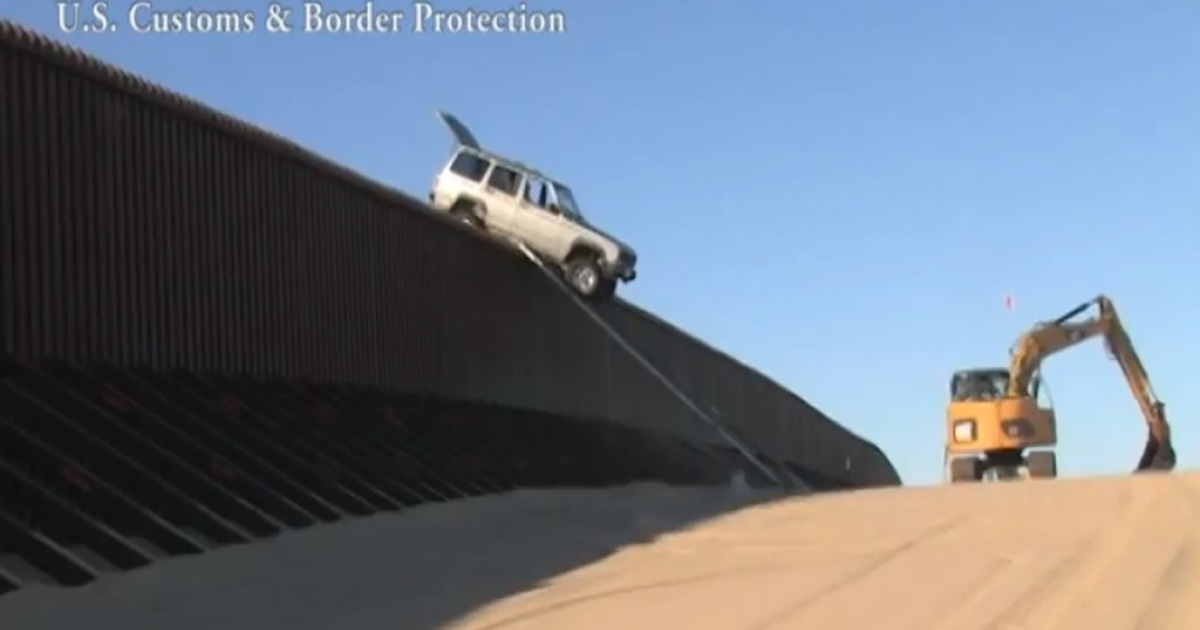 US Customs &amp; Border Protection agents remove the Jeep from the fence.</p>