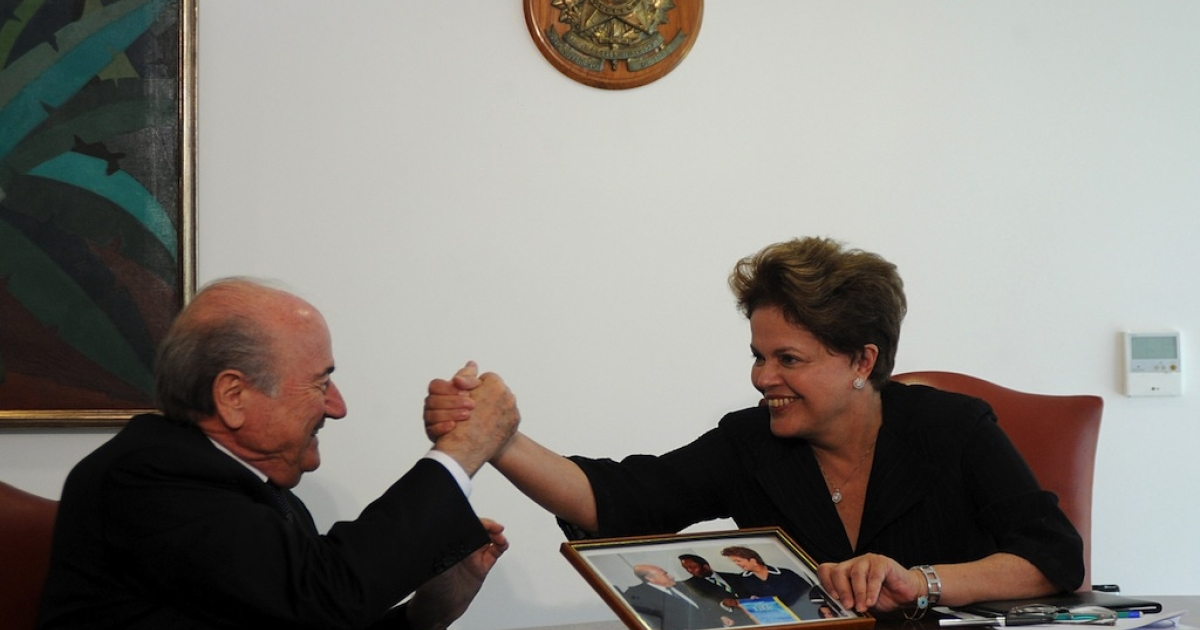 Brazilian President Dilma Rousseff (R) shakes hands with FIFA President Joseph