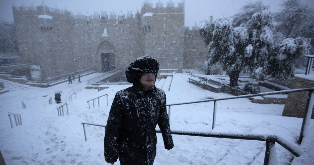 An ultra-orthodox Jewish man runs as snow falls next to Damascus gate in the old city of Jerusalem on January 10, 2013.</p>