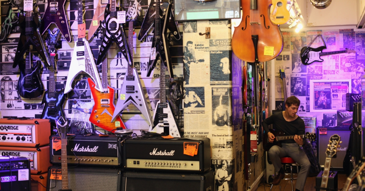 A customer tries out a guitar and amplifier in a shop in London, England. Jim Marshall, the creator of the legendary Marshall guitar amp, died Thursday at age 88.</p>