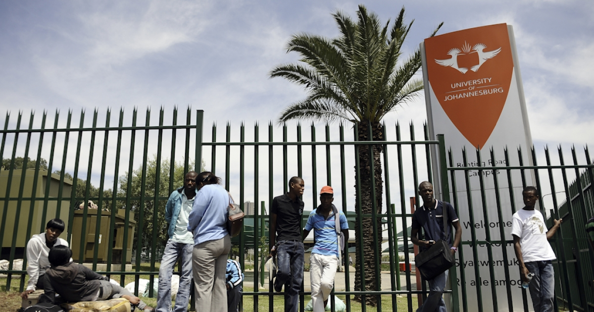 Students queue outside the University of Johannesburg to register for this year's studies on January 10, 2012. This morning a stampede broke out leaving one person dead and at least three critically injured. Aspiring students have been queuing outside the university since the early hours of January 9, hoping to submit late applications. Many had brought umbrellas and chairs and camped there overnight. About 74,000 students will be turned away from the University of Johannesburg this year. Last year, the university processed 85,000 applications for 11,000 first-year spots.</p>