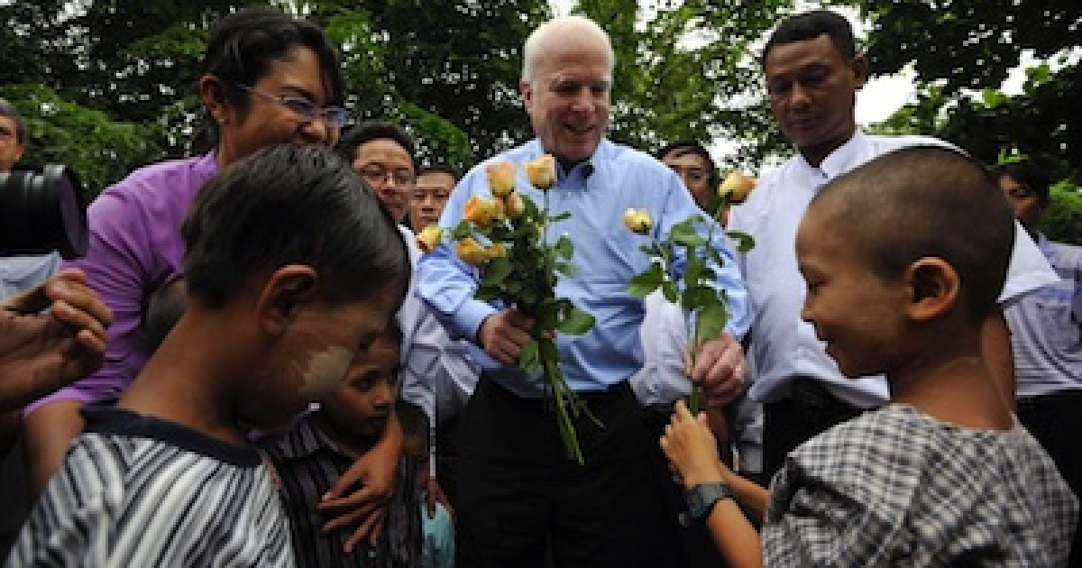 U.S. Senator John McCain receives flowers from an unidentified HIV-infected child during a visit to a private HIV/AIDS care center run by members of the National League for Democracy political party in Yangon, Myanmar.</p>