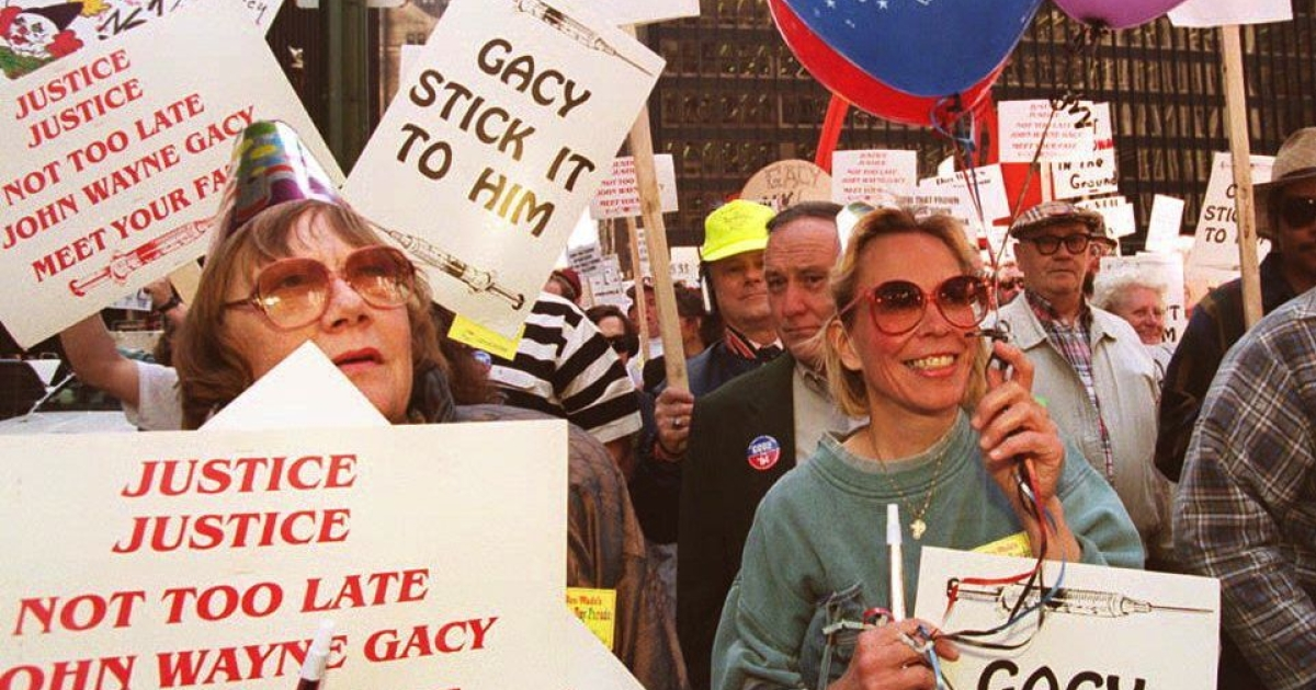 Supporters of the scheduled execution of serial killer John Wayne Gacy hold balloons and wear party hats as they march in a Gacy Day Parade May 9, 1994 in Chicago.</p>