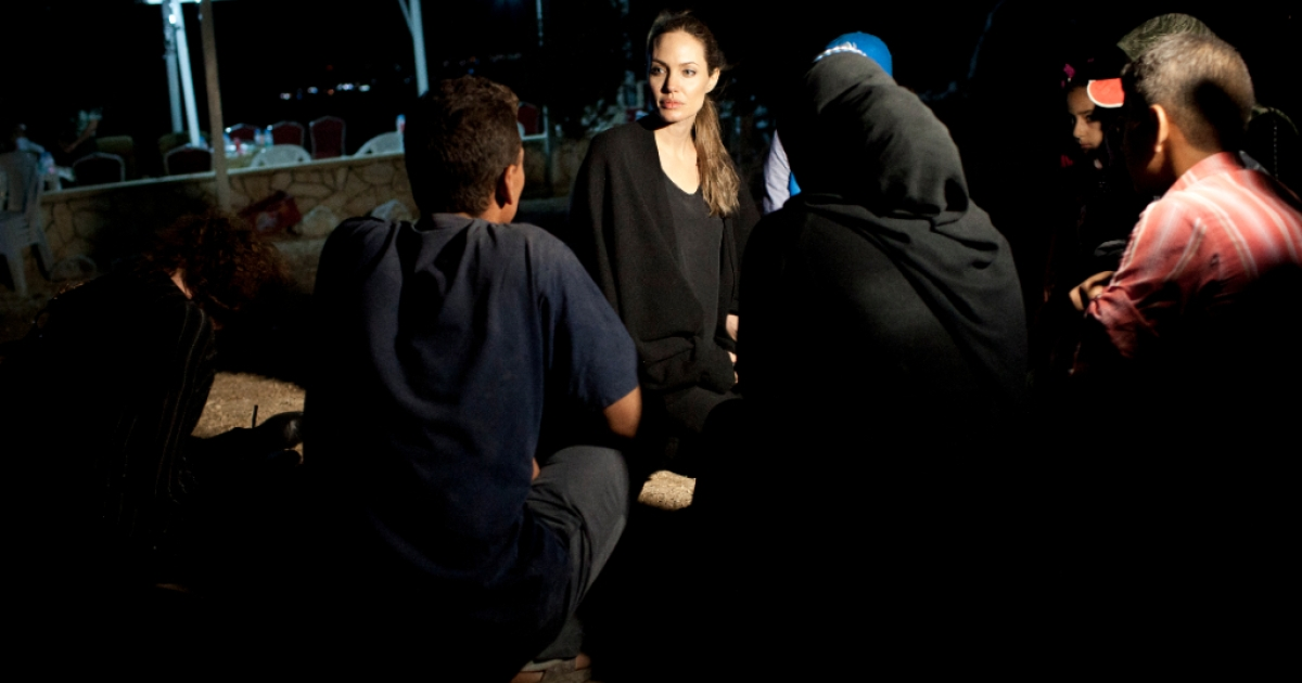 In this handout image provided by UNHCR, UNHCR Special Envoy Angelina Jolie meets with refugees on the Jordanian border minutes after they crossed from Syria on September 10, 2012 in Amman, Jordan. With shelling clearly audible and visible across the border in Syria, some 200 refugees made the dangerous crossing under cover of night. Authorities estimate hundreds of families are fleeing the violence and seeking safety across the border every night.</p>