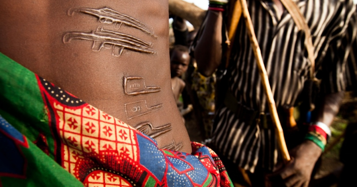 A Jie warrior with scars designed to look like AK-47s. He and his friend prepare for battle with the neighboring Murle tribe. Previous generations had scars representing wild animals and abstract symbols of power. Now, guns and satellite phones are common showing how deeply guns have become a symbol and tool for holding onto power.</p>