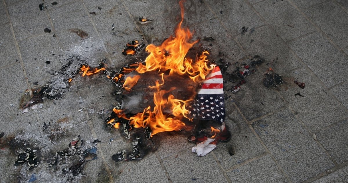 Protesters in London set fire to an American flag in 2010.</p>