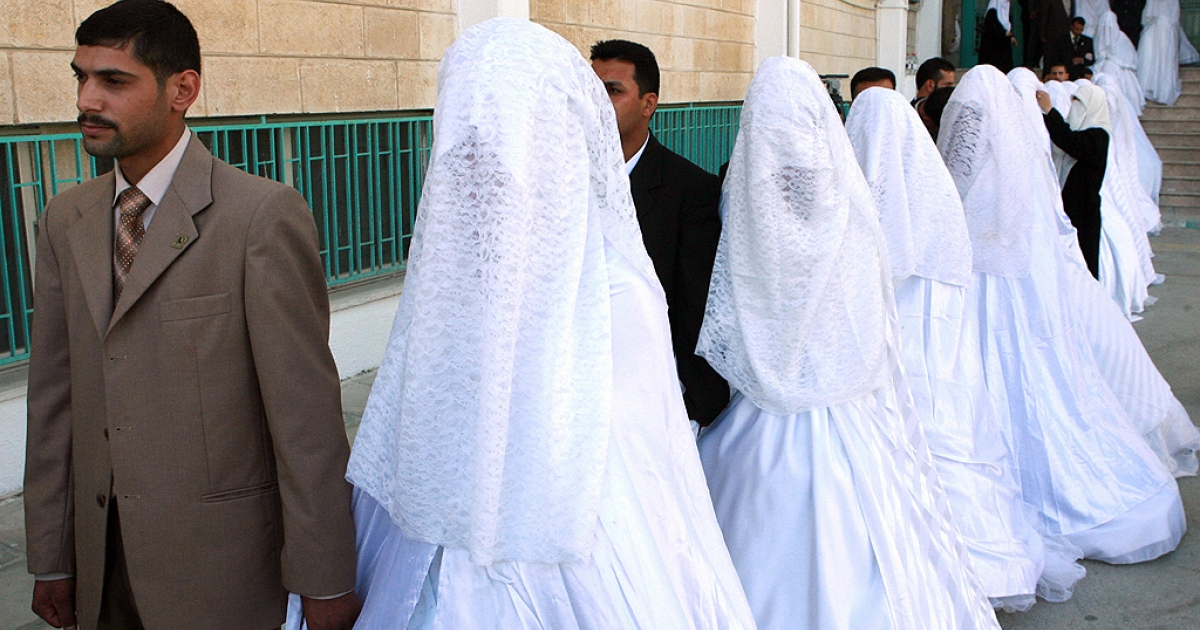 Jordanian couples form a long line as they take part in a mass wedding party in the Jordanian capital Amman, on July 20, 2007. A Jordanian Islamic charity Al-Afaf today organised a mass wedding for 32 couples to help young people unable to afford the expensive ceremonies that the Arab tradition usually demands.</p>