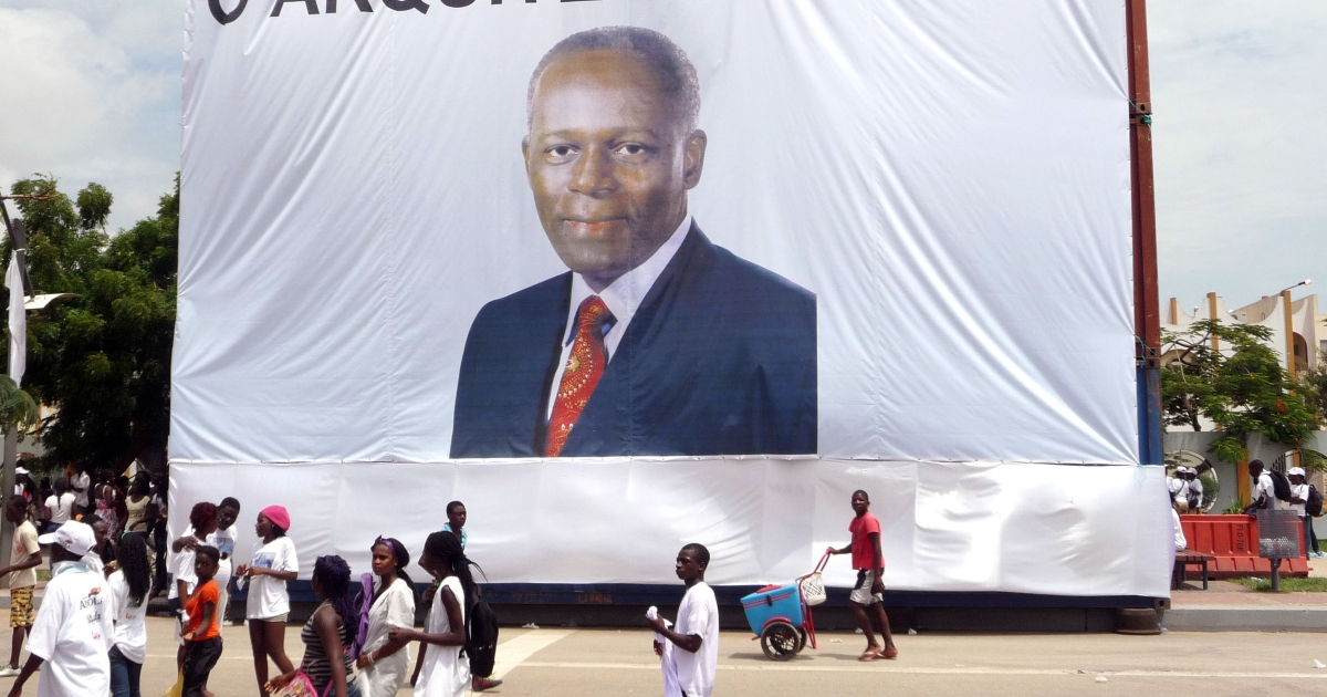 People walk in front of a large portrait of Angolan President Jose Eduardo de Santos with text reading 'The Architect of Peace', in the streets of Luanda on April 4, 2012.</p>