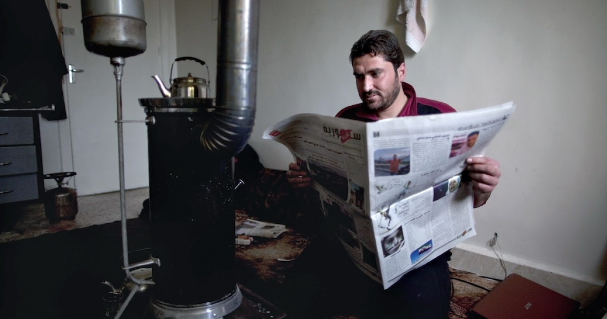 Khaled al-Khatib, editor of Suria Al-Hurra (Free Syria), posing with an issue of the month-old weekly newspaper which he runs with a small group of journalists in Syria's rebel-held territories. Pictured here on Jan. 6, 2013 in Aleppo, northern Syria.</p>