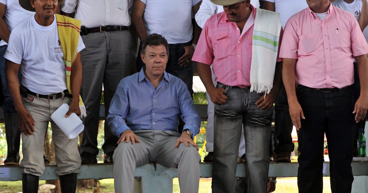 Colombian President Juan Manuel Santos, sitting, is surrounded by farmers during a recent event in the Vichada department, eastern plains of Colombia.</p>