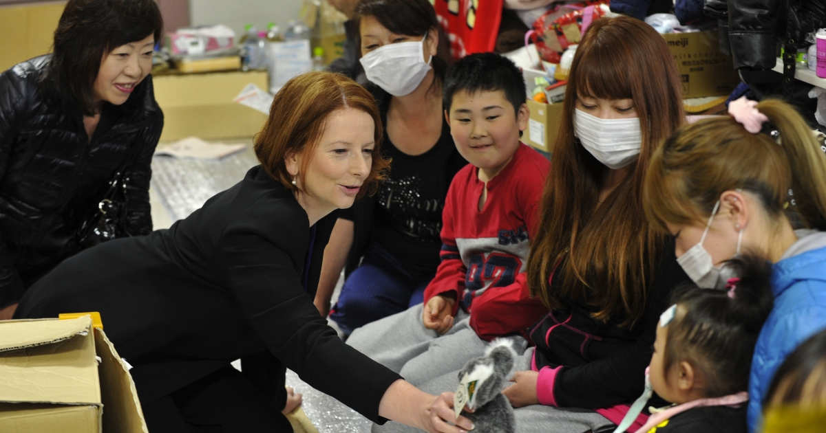 Australian Prime Minister Julia Gillard (C) presents a toy koala to a child during a visit to a tsunami survivor's shelter in the town of Minamisanriku, Miyagi prefecture on April 23, 2011.</p>