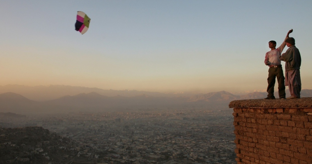 Afghan boys fly a kite on a hill overlooking Kabul.</p>