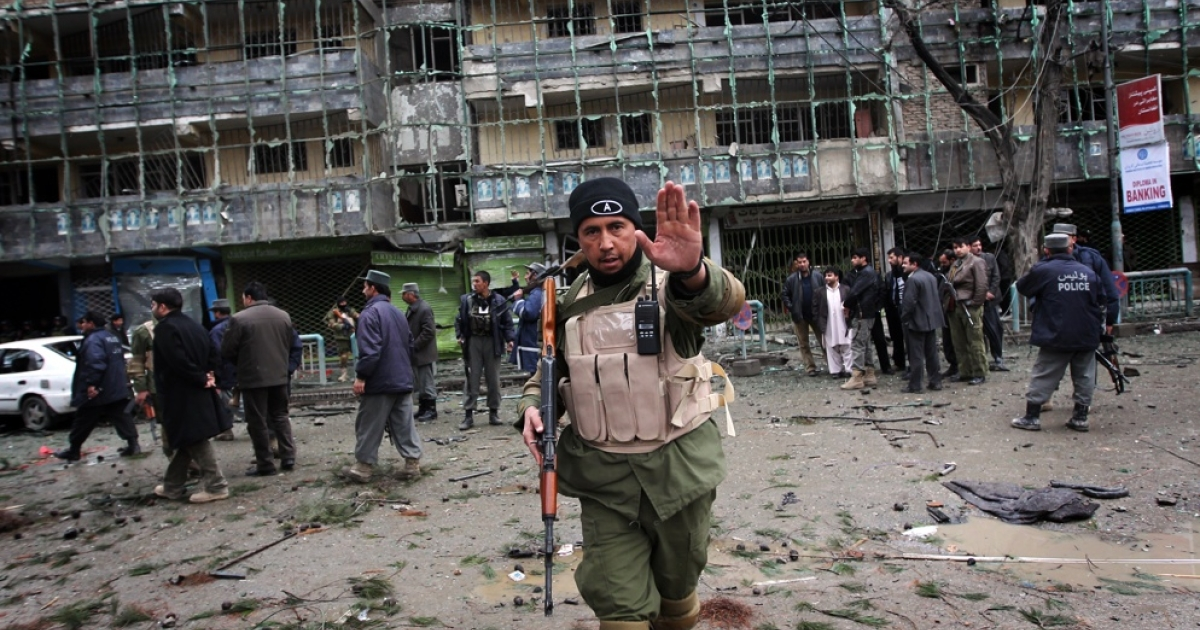 An Afghan security officer tries to stop photographers from taking pictures outside the Park Residence guesthouse in Kabul after a suicide bombing on Feb. 26, 2010.</p>