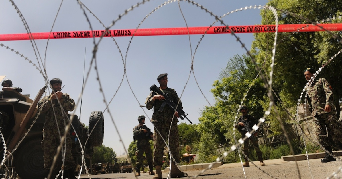 Members of the Afghan military stand guard near barbed wire on the road which leads towards a military hospital in central Kabul on May 21, 2011.</p>