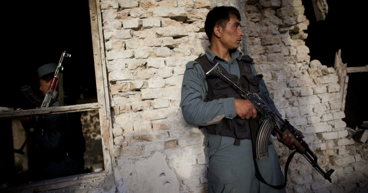 An Afghan police officer secures a building attacked by the Taliban on May 14, 2011 in Kandahar, Afghanistan.</p>