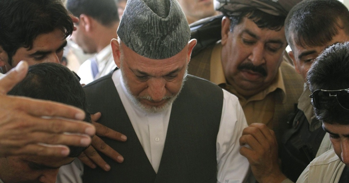 Afghan President Hamid Karzai attends the last memorial service of his brother Ahmad Wali Karzai in Dand district of Kandahar province on July 13, 2011.</p>
