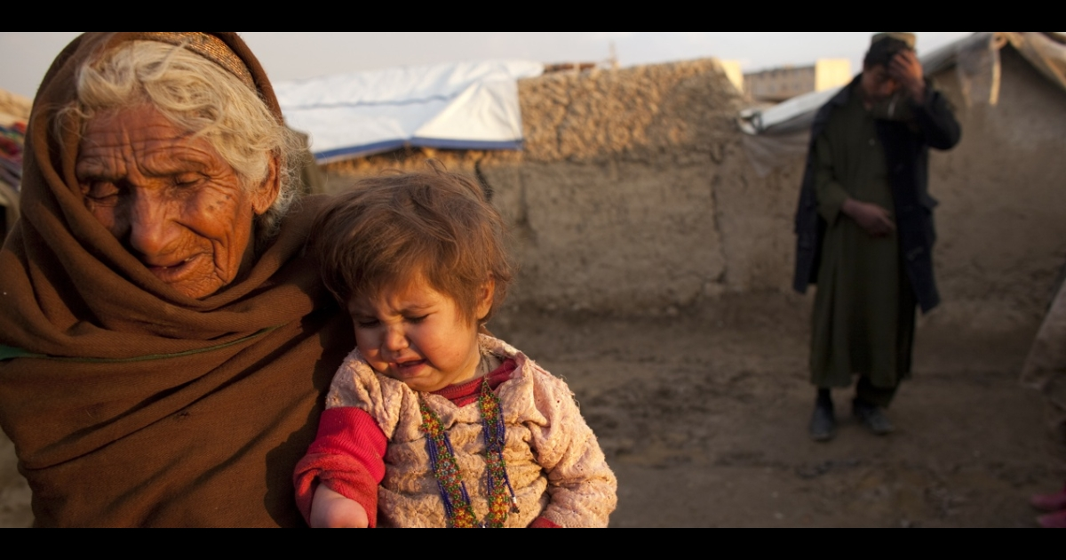 An Afghan civilian holds her granddaughter, who lost part of her arm during a recent US attack, outside a crowded refugee camp near Kabul in 2009.</p>