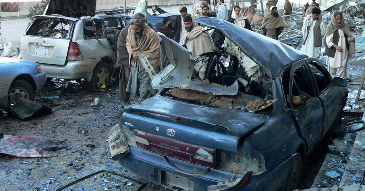 Afghan bystanders inspect damaged vehicles at the site of an attack by suicide bombers in Kandahar on February 15, 2011.</p>