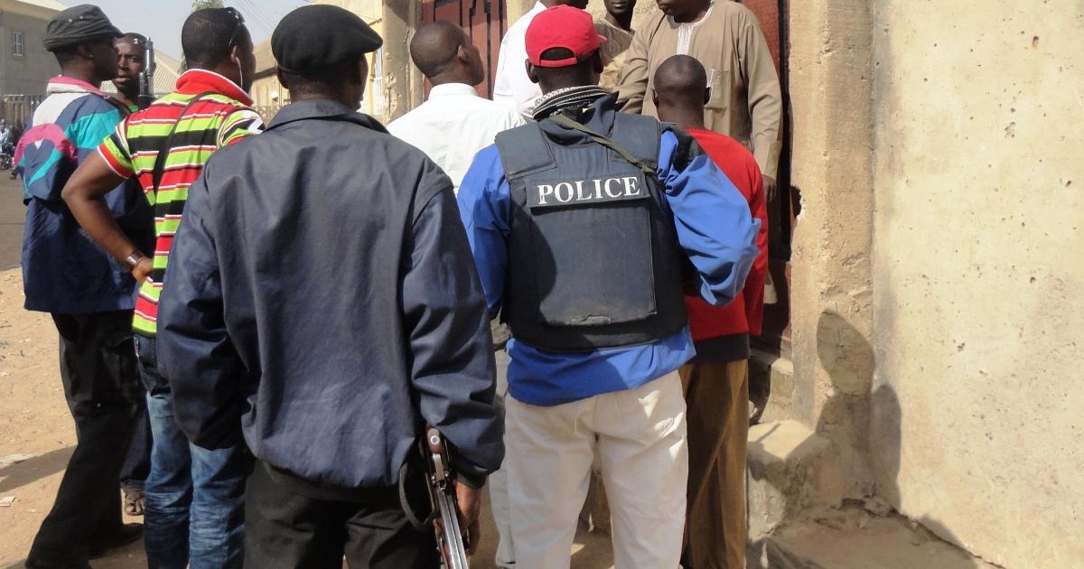 Police officers enter the house of a suspected member of the Nigerian Islamist group Boko Haram, Uzairu Abba Abdullahi, in the Tsamiyar Boka neighborhood of Kano on Jan. 24, 2012.</p>