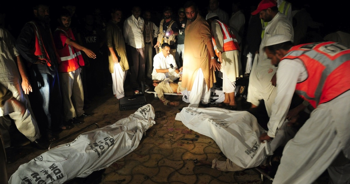 Pakistani volunteers remove the bodies of three suicide bombers that blew themselves up in their car when intercepted by police in Karachi on November 16, 2011. The bombing took place in the upscale Karachi Sea View neighborhood.</p>