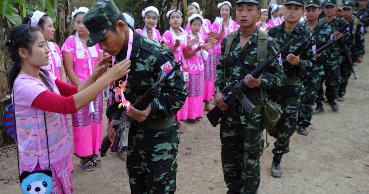Karen women (L) dressed in traditonal clothing present garlands to Karen National Union (KNU) soldiers during the celebration of 63rd anniversary of the Karen Revolution day in Karen State, near the Thai-Myanmar border on January 31, 2012.</p>