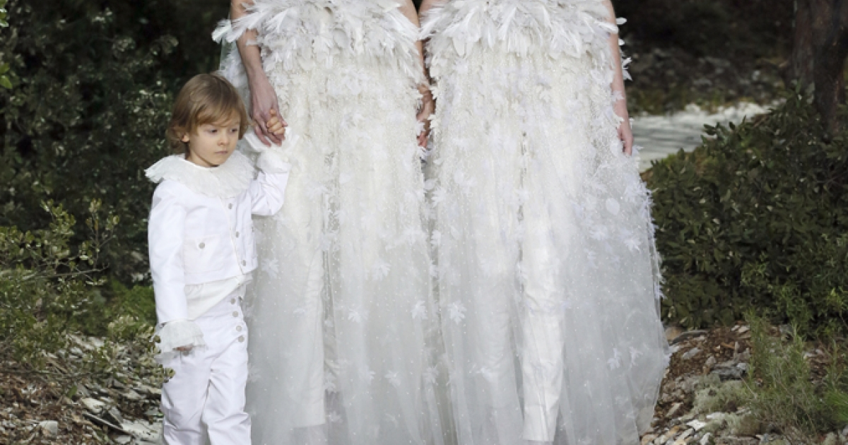 Models present creations for Chanel with Hudson Kroenig, German designer Karl Lagerfeld's godson, during the Haute Couture Spring-Summer 2013 collection shows on Jan. 22, 2013 at the Grand Palais in Paris.</p>