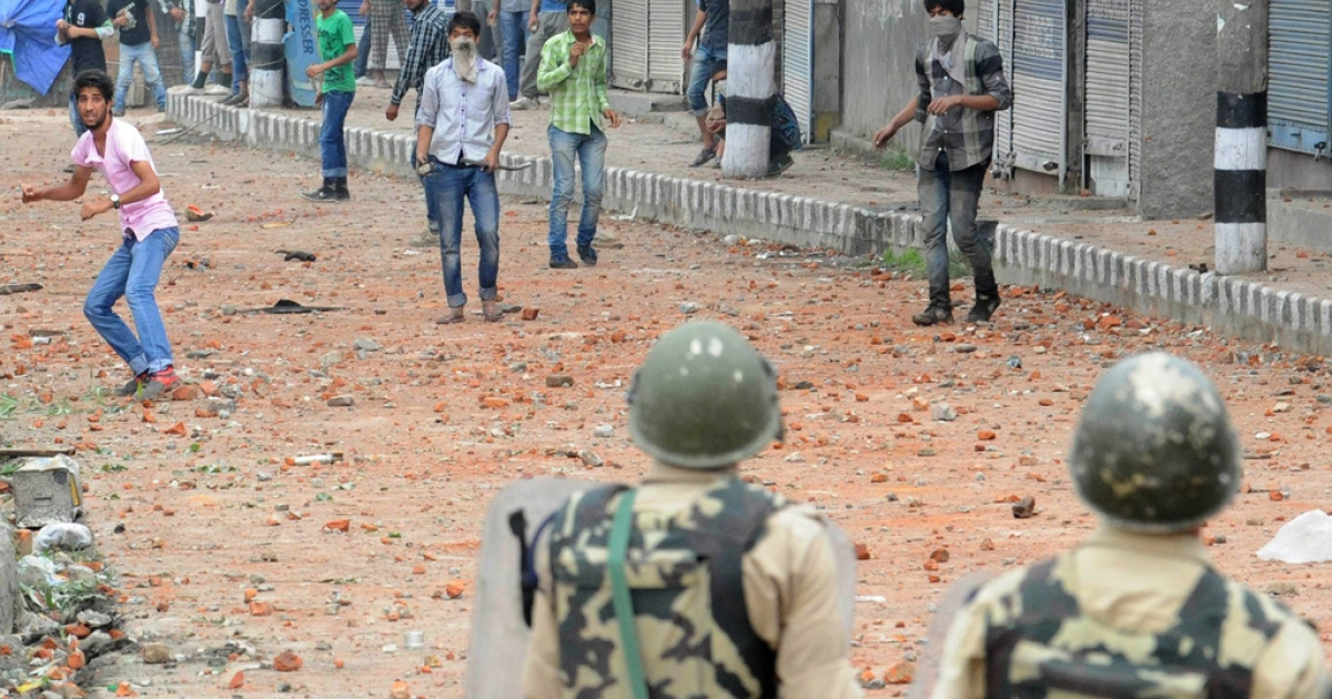 A Kashmiri Muslim protester throws a stone at Indian police during a demonstration, after a fire broke out at the 200 year old heritage Sufi shrine of Sheikh Abdul Qadir Jeelani in downtown Srinagar on June 25, 2012. The fire gutted the 200-year-old revered Sufi Muslim shrine, sparking clashes between police and residents in capital city, triggered by anger at the perceived delayed response of firefighters in battling the blaze.</p>