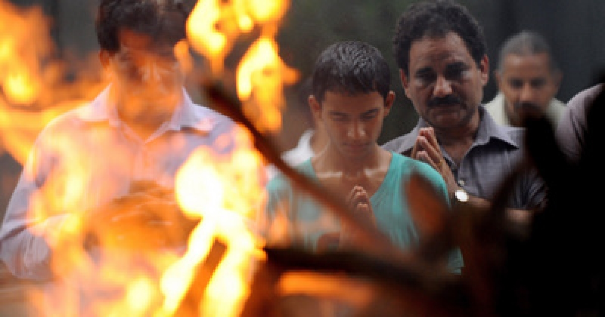 Rishabh the son of A. K. Sharma, a school teacher who was killed in bomb blast outside Delhi high court, prays during his fathers cremation in New Delhi on September 8, 2011. Police in Indian Kashmir questioned three men in connection with a deadly bombing at New Delhi's High Court, as the prime minister acknowledged systemic