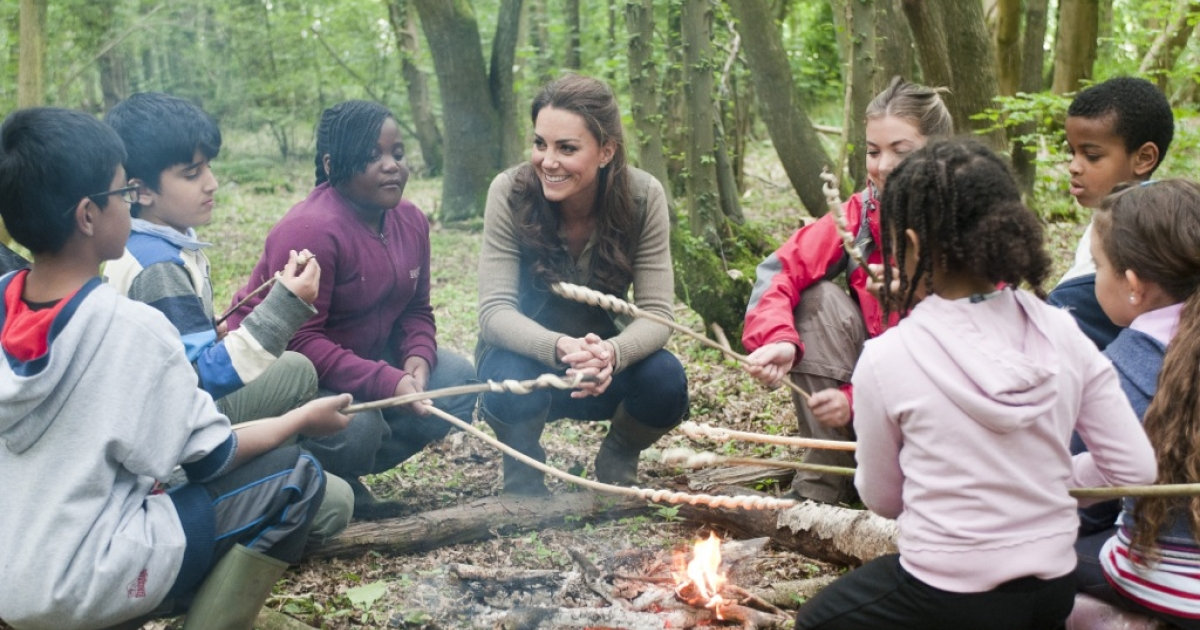 Catherine, Duchess of Cambridge, takes part in a campfire with children as she visits the 'Expanding Horizons' Primary school camp at Margaret MacMillan house in Wrotham, Kent, on June 17, 2012.</p>