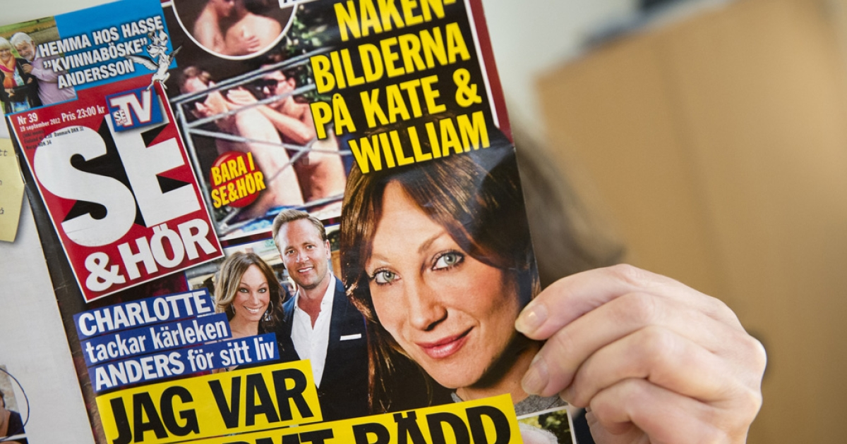 A woman holds a copy of the celebrity magazine Se &amp; Hor in Stockholm on September 20, 2012,  showing Britain's Prince William and a topless Princess Kate taken while on holiday in France on September 5.</p>